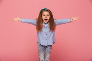 Cheerful little girl in hair hoop posing with open hands against